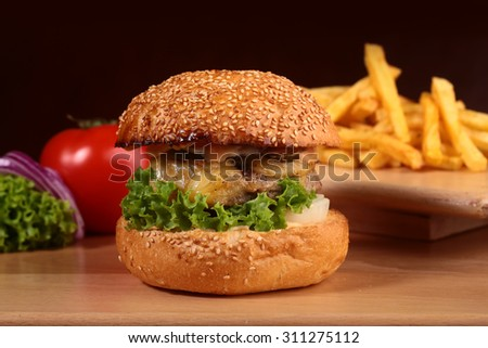 One big delicious fresh burger of green lettuce red tomato cheese meat cutlet violet oinion and white bread bun with sesame seeds on black background closeup, horizontal picture - stock photo