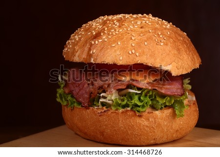 One big delicious fresh burger with green lettuce red tomato cheese cabbage bacon slice meat cutlet and white bread bun with sesame seeds on black background closeup, horizontal picture - stock photo