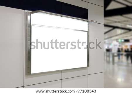 One big horizontal / landscape orientation blank billboard on modern white wall with subway concourse background - stock photo