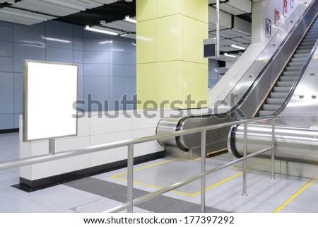 One big vertical / portrait orientation blank billboard in public transport with escalator and blurred passenger background - stock photo