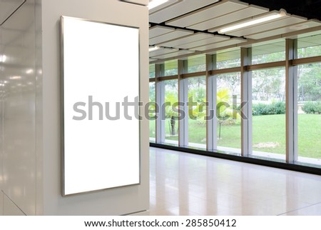 One big vertical / portrait orientation blank billboard on modern white wall with corridor background - stock photo