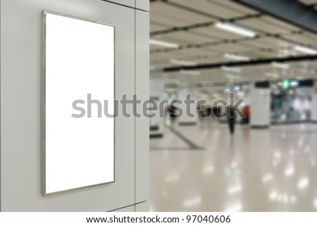 One big vertical / portrait orientation blank billboard on modern white wall with subway concourse background - stock photo