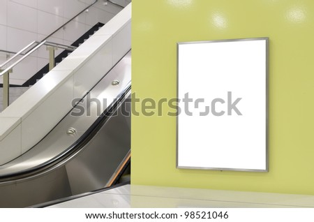 One big vertical / portrait orientation blank billboard on modern yellow wall with escalator background - stock photo