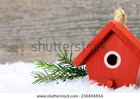 One birdhouse on snow with wooden background - stock photo