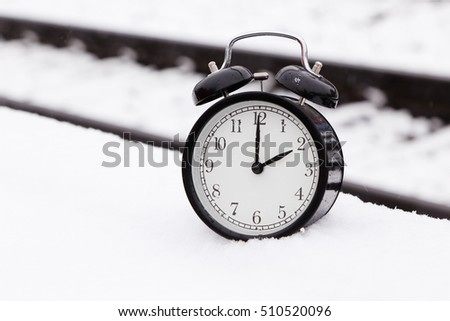 One black alarm clock at railroad tracks outdoors in snow.
