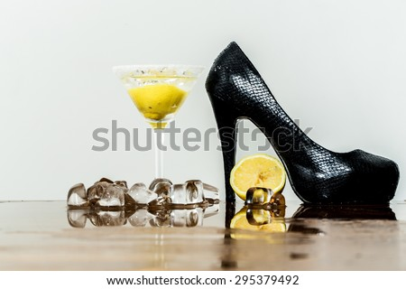 One black leather shoe on high heel wine glass with water and yellow lemon ice cubes on table top on white background, horizontal picture - stock photo