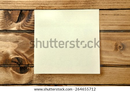 one blank postnote on wood background
