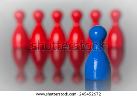 One blue figure in front of many red figures. Frontman.  - stock photo