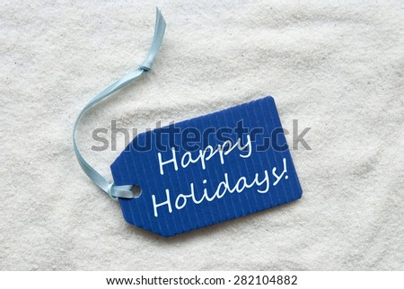 One Blue Label Or Tag With Light Blue Ribbon On White Sand Background With English Text Happy Holidays - stock photo