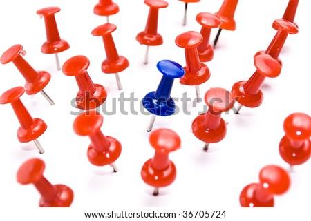 One blue thumbtack amid red thumbtacks. Selective focus - stock photo