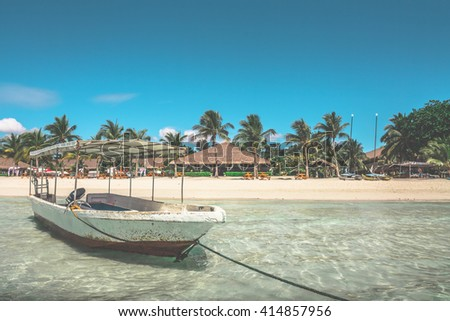 One boat floating in the transparent sparkling ocean water against background with white sand beach,palm forest  and luxury bamboo huts,clear blue sky on a sunny summer day.Panglao island,Philippines. - stock photo