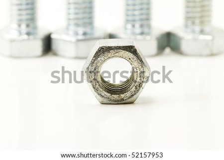 one bolt in front of four screws on white background