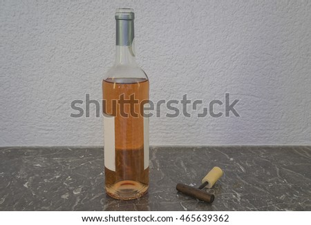 One bottle of pink wine and one corkscrew on a marble background
