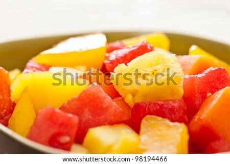 One bowl of Mixed tropical fruit salad in front of nature a background - stock photo