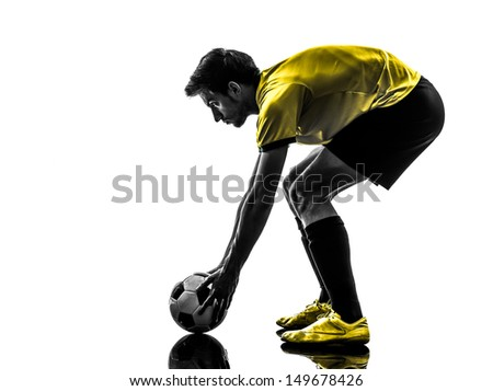one brazilian soccer football player young man preparing free kick in silhouette studio  on white background - stock photo