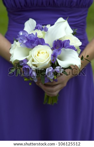 one bridesmaid in purple holding a wedding bouquet
