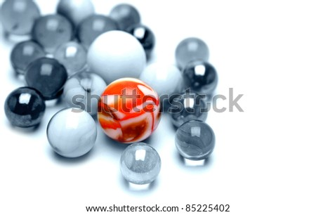 One bright marble standing out from the crowd - stock photo
