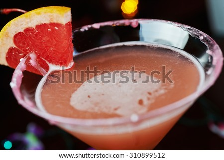 one bright refreshing cocktails on a table in a restaurant with creative decoration of red orange slices on a wooden table in a bar with a beautiful disco lights bokeh in the background. soft focus. - stock photo