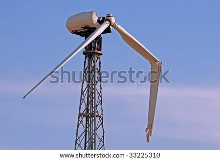 one broken wing on a single wind turbine against a blue sky - stock photo