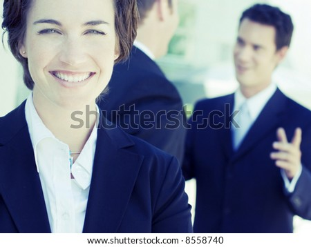 one business woman staring at camera while two businessmen talk in background - stock photo