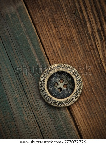 one Button for clothes on an old wooden surface of board. instagram image retro style