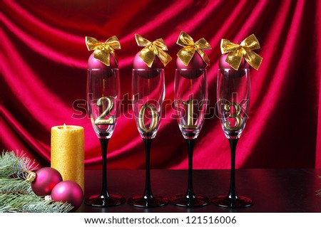 One candle and four  goblets of champagne with numeral 2013 against purple drapery. Happy New Year! - stock photo