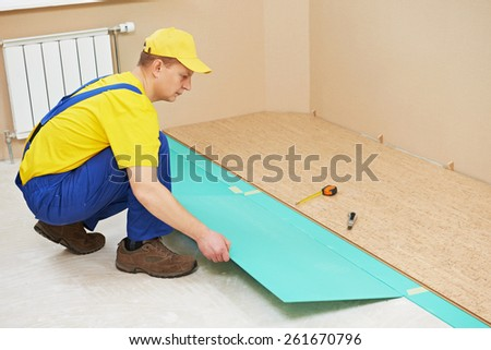 One carpenter worker laying cork boards during indoors flooring work - stock photo
