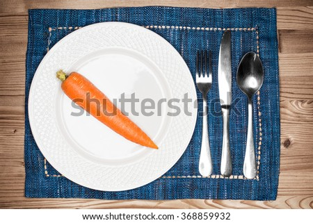 One carrot on an empty white plate for diet or health - stock photo