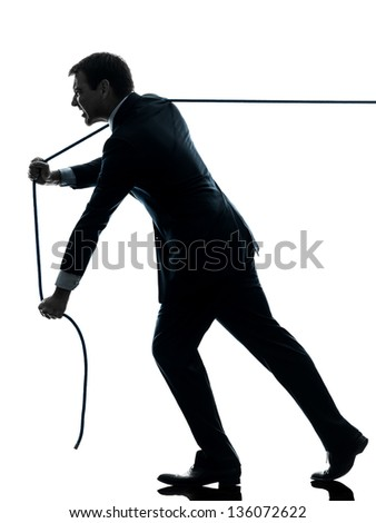one caucasian business man pulling a rope in silhouette studio isolated on white background - stock photo