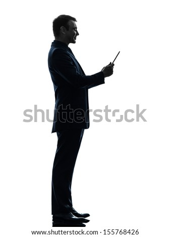 one caucasian business man smiling  holding digital tablet   in silhouette on white background - stock photo