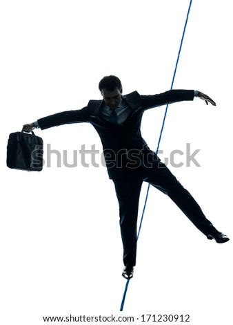 one caucasian Businessman tightrope walker in silhouette studio isolated on white background - stock photo