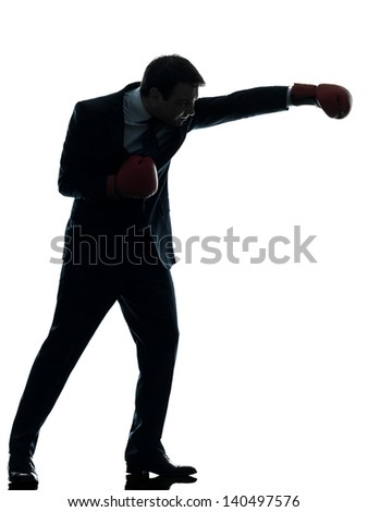 one caucasian businessman with boxing gloves   in silhouette studio isolated on white background
