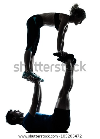 one caucasian couple man woman personal trainer coach exercising acrobatic silhouette studio isolated on white background - stock photo