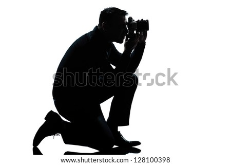one caucasian man kneeling photographer full length silhouette in studio isolated on white background