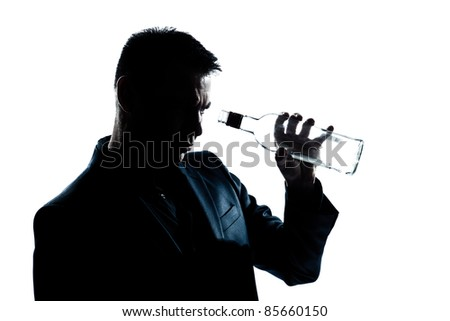 one caucasian man portrait silhouette drunk looking at an empty alcohol botlle in studio isolated white background - stock photo