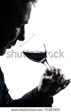 one caucasian man portrait silhouette smelling red wine glass in studio isolated white background - stock photo