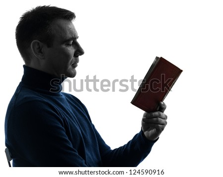 one caucasian man reading book portrait in silhouette studio isolated on white background - stock photo