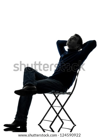 one caucasian man sitting resting looking up  full length in silhouette studio isolated on white background - stock photo