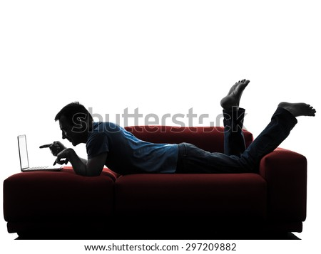 one caucasian man sofa couch computer computing laptop in silhouette isolated on white background - stock photo