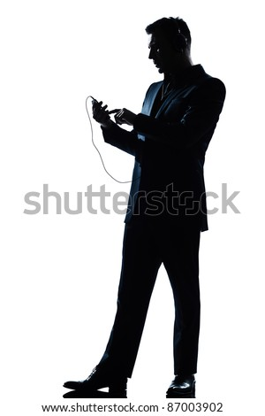 one caucasian man text messaging telephone listening to music full length silhouette in studio isolated white background - stock photo