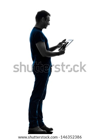 one caucasian man touchscreen digital tablet   in silhouette on white background - stock photo