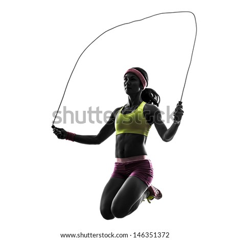 one caucasian woman exercising fitness  jumping rope  in silhouette on white background - stock photo