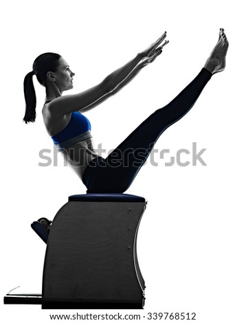 one caucasian woman exercising pilates chair exercises fitness in silhouette isolated on white backgound - stock photo