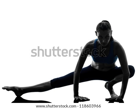 one caucasian woman exercising yoga stretching legs warm up in silhouette studio isolated on white background - stock photo