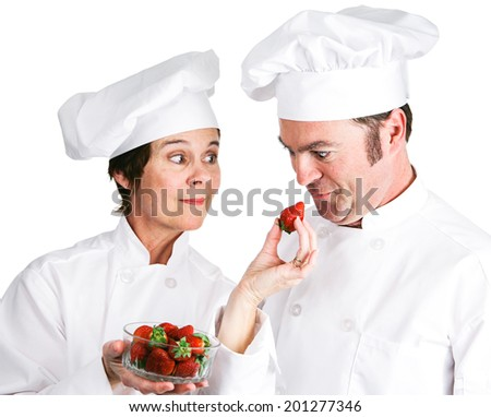 One chef offers another a fresh strawberry.  Isolated on white.
