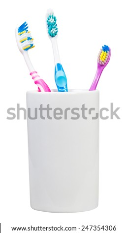 one children and two adult tooth brushes in ceramic glass - family set of toothbrushes isolated on white background - stock photo
