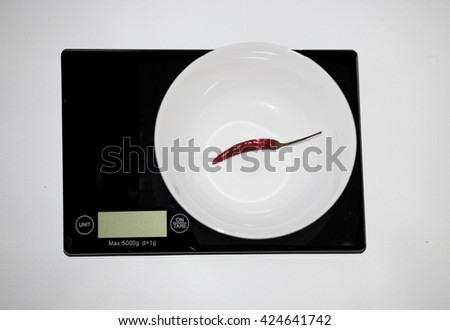 One chili on a digital white kitchen scale. (weighing products) - stock photo