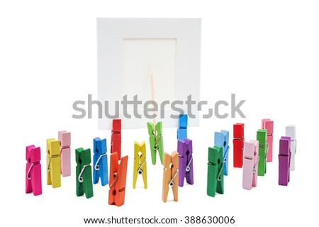 One clothespin standing and shows a toothpick on a white blank form to a group of pegs - stock photo