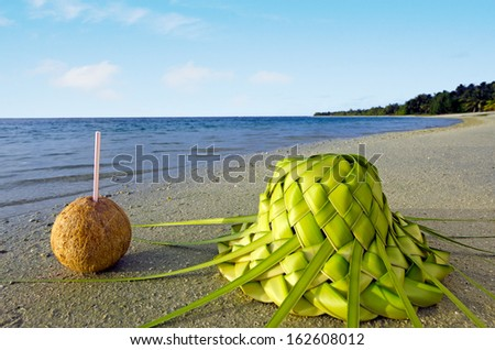One coconut and sun hat knees out of palm leaves on sandy sea shore of tropical island. - stock photo