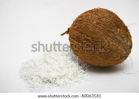 One coconut on isolated white background, with shredded pulp on side.
